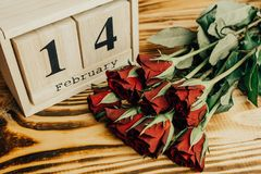 Conceito mínimo do dia de Valentim do St no fundo de madeira Rosas vermelhas e caledar de madeira com o 14 de fevereiro nele Fotografia de Stock Royalty Free