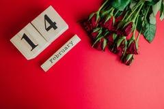 Conceito mínimo do dia de Valentim do St no fundo vermelho Rosas vermelhas e caledar de madeira com o 14 de fevereiro nele Fotografia de Stock Royalty Free
