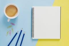 Conceito mínimo do local de trabalho do escritório Caderno vazio, xícara de café, lápis, clipe de papel no fundo amarelo e azul Fotos de Stock
