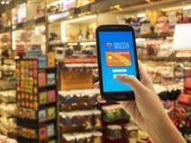 Conceito móvel da carteira na tela esperta do telefone sobre a loja do borrão foto de stock royalty free