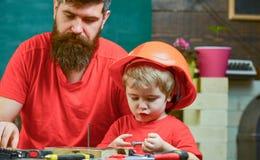 Conceito masculino dos deveres Menino, criança ocupada no capacete protetor aprendendo a martelar cravos com paizinho Pai, pai imagens de stock