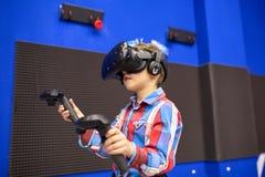 Conceito moderno da tecnologia, do jogo e dos povos - menino nos auriculares da realidade virtual ou nos vidros 3d que jogam o vi imagens de stock