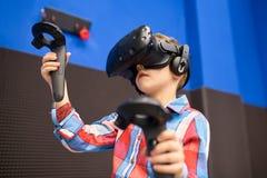 Conceito moderno da tecnologia, do jogo e dos povos - menino nos auriculares da realidade virtual ou nos vidros 3d que jogam o vi foto de stock