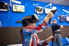 Conceito moderno da tecnologia, do jogo e dos povos - menino nos auriculares da realidade virtual ou nos vidros 3d que jogam o vi imagem de stock