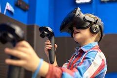 Conceito moderno da tecnologia, do jogo e dos povos - menino nos auriculares da realidade virtual ou nos vidros 3d que jogam o vi fotografia de stock royalty free