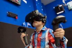 Conceito moderno da tecnologia, do jogo e dos povos - menino nos auriculares da realidade virtual ou nos vidros 3d que jogam o vi imagens de stock royalty free