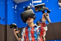 Conceito moderno da tecnologia, do jogo e dos povos - menino nos auriculares da realidade virtual ou nos vidros 3d que jogam o vi foto de stock royalty free