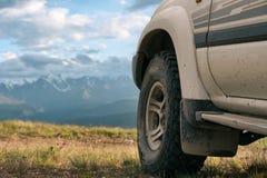 Conceito Offroad do carro com montanhas Close-up da roda Fotos de Stock Royalty Free
