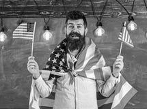 Conceito patriótico da educação Programa da troca do estudante O professor americano acena com bandeiras americanas Homem com bar imagens de stock royalty free