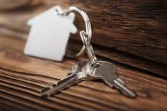 Conceito, porta-chaves e chaves dos bens imobiliários no fundo de madeira Foto de Stock Royalty Free
