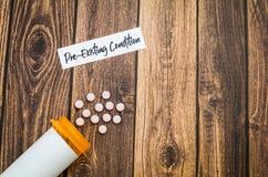 Conceito Pre-existente dos cuidados médicos da circunstância com os comprimidos na placa de madeira fotografia de stock