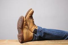Conceito preguiçoso da pessoa: os pés do homem que vestem a calças de ganga de botas de deserto descansam em uma tabela de mad fotografia de stock royalty free
