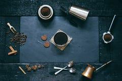 Conceito - preparação do café Copo de café, mocha, fabricante de café, feijões roasted, colheres, cezve do turkisch, biscoitos e  imagem de stock