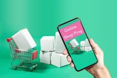 Conceito que compra em linha: Mão que guarda o telefone esperto para w de compra fotos de stock royalty free