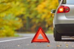 Conceito quebrado do carro, sinal da parada do triângulo da divisão na estrada Imagens de Stock Royalty Free