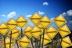 Conceito regulamentar no sinal de estrada amarelo com céu azul foto de stock