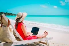 Conceito remoto do trabalho - jovem mulher com o portátil na praia imagem de stock