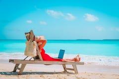 Conceito remoto do trabalho - jovem mulher com o portátil na praia imagens de stock