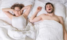 Conceito ressonando A jovem mulher está cobrindo suas orelhas O homem está ressonando na cama Fotografia de Stock