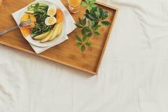 Conceito saudável comer Mulher que come o pequeno almoço na cama Fotos de Stock Royalty Free