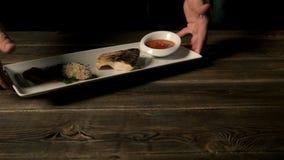 Conceito saudável do alimento: Parte cozida quente dos peixes do serviço principal sobre a placa branca na tabela de madeira filme