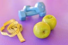 Conceito saudável do estilo de vida - maçã verde com pesos e a fita de medição amarela fotografia de stock