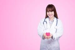 Conceito saudável: Doutor asiático novo com coração vermelho à disposição fotos de stock royalty free