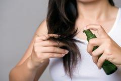 Conceito saudável A terra arrendada da mão da mulher danificou o cabelo longo com tratamento do cabelo do óleo imagens de stock
