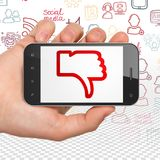 Conceito social da rede: Entregue guardar Smartphone com polegar para baixo na exposição Foto de Stock
