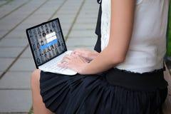 Conceito social da rede - próximo acima do portátil nas mãos fêmeas com imagens de stock