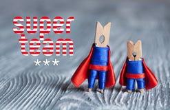 Conceito super da equipe Super-herói do Peg do pregador de roupa no terno azul e no cabo vermelho Fundo abstrato de madeira cinze fotos de stock royalty free