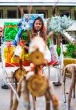 Conceito tropical do Natal Jovem mulher no pequeno trenó de Santa Claus com os presentes coloridos brilhantes Foto de Stock Royalty Free