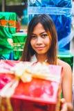 Conceito tropical do Natal Jovem mulher no pequeno trenó de Santa Claus com os presentes coloridos brilhantes Imagens de Stock