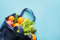 Conceito waste zero Saco de compra azul de matéria têxtil de algodão com laranja e os vegetais frescos Espaço para o texto fotografia de stock royalty free