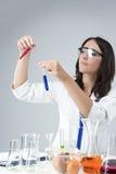 Conceitos da medicina e da ciência Pesquisador fêmea caucasiano Compares Substances em duas garrafas separadas Imagens de Stock