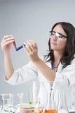 Conceitos da medicina e da ciência Pesquisador fêmea caucasiano Compares Substances em duas garrafas separadas Foto de Stock