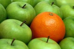 Conceitos diferentes - laranja entre maçãs fotografia de stock royalty free