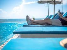 Conceitos do curso, os pés dos homens que descansam em uma piscina e que usam o telefone esperto Conceito de viagem das f?rias de fotografia de stock