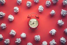 Conceitos do desempenho com a bola e o despertador amarrotados de papel no fundo do worktable Hora e linha da data imagens de stock royalty free