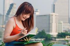 Conceitos do negócio A mulher de negócio asiática é de leitura e de escrita livros imagens de stock