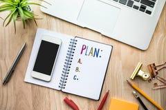 Conceitos do plano de negócios com papel do bloco de notas na tabela e em fontes de madeira fotos de stock royalty free