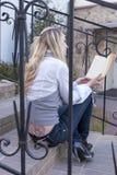 Conceitos e ideias da leitura Retrato da fêmea loura caucasiano tranquilo com o livro que senta-se em escadas fora e na leitura Fotografia de Stock
