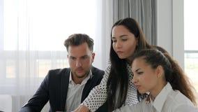 Conceituar, os gerentes perto da tela do portátil que falam um com o otro, os trabalhadores criativos que discutem o desenvolvime filme