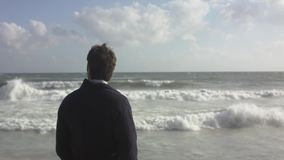 A conceived man walking on ocean beach stock video footage