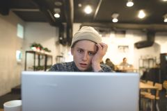 Conceived young man looks at the monitor of his laptop in a cozy cafe for a cup of coffee. The freelancer works in a cafe Royalty Free Stock Images