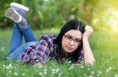 Conceived young woman lying on grass Stock Photos