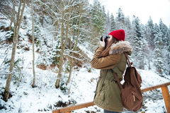 Concenrated woman photographer standing and taking pictures in mountains Stock Image