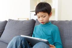 Concentré de petit garçon de l'Asie sur le comprimé Photo libre de droits