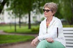 A concentré toute la femme supérieure européenne de pensées en verres d'oeil Se reposer sur le banc en parc et le regard loin, co Image libre de droits