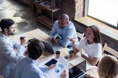 Concentración completa en el trabajo Grupo de hombres de negocios jovenes que trabajan y que comunican mientras que se sienta en  imagen de archivo